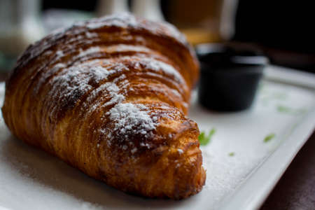 croissant in powdered sugar on a white plate. apricot jam in a black little plate next to a croissant