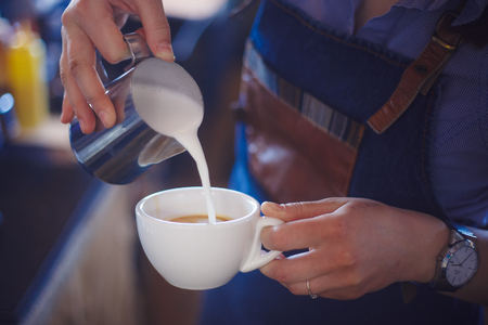 baristas: baristas prepares an elegant cappuccino