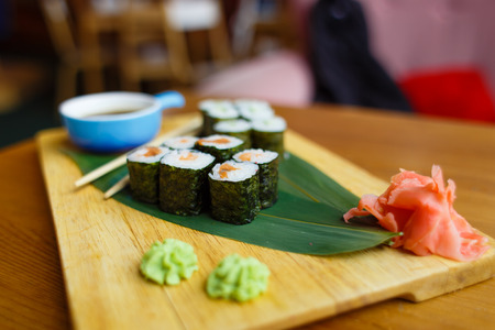 Sushi with a cucumber on a wooden board