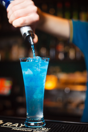 The bartender pours a drink on a cold glass closeup