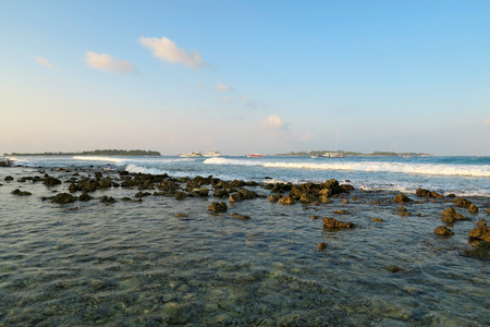 Jailbreaks surfing spot with waves in evening on Himmafushi island, Maldives