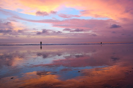 Beautiful Balinese sunset at Kuta beach with peoples and sky reflection in sand