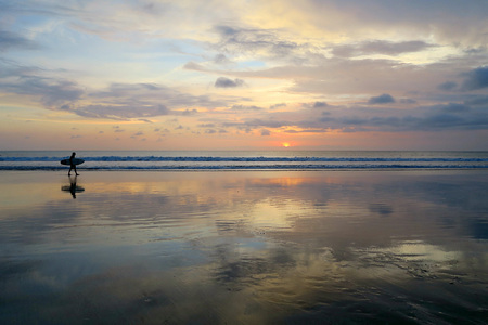 Lonely surfer silhouette walking along empty Kuta beach with sunset sky Stock Photo