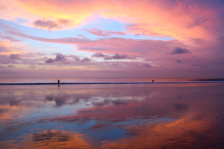 Beautiful Balinese sunset at Kuta beach with peoples and sky reflection in wet sand Stock Photo