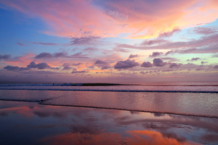 Violet sky and mirror reflection sunset at Kuta beach, Bali, Indonesia