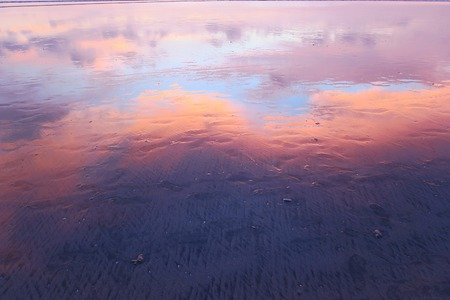 Pink clouds reflection in wet sand of Kuta beach, Bali Stock Photo