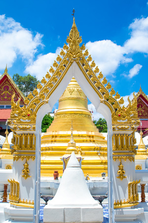 The temple gate decorated with a beautiful Thai style, the back is the old golden pagoda in the temple area.The temple is place of religious importance and public place for general people.