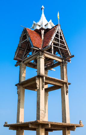 The old bell tower has white peaks and the roof is brown. This place is a public place with lots of people visiting at this. Stock Photo