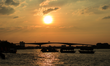 Dark shadow of boats floating in the river have ferry bridge at sunset time. Stock Photo