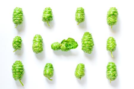 Bovenaanzicht van groene Morinda citrifolia l. met knoestige huid op een witte ondergrond.