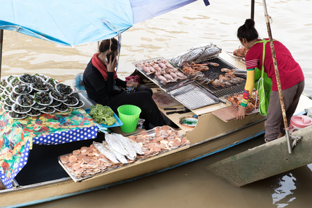 Amphawa,Samut Songkhram,Thailand-June 11.2017: Female trader sells seafood on the grill in boat of Amphawa Floating Market canal. Editorial