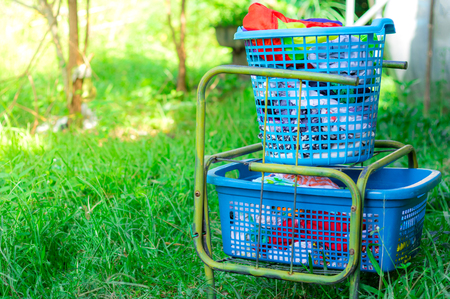 Washed clothes in the old basket stacked to wait hang for the sun. Stock Photo