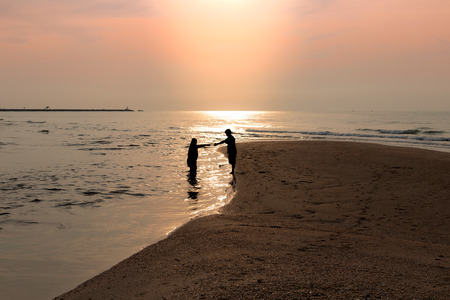 Silhouette of the couple held hands together at the seashore. Reflection of the sun on water surface. During in the morning with warm sunlight. Stock Photo