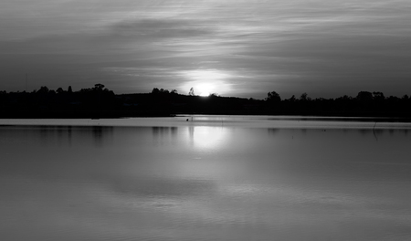 Low light view with black and white of quiet freshwater lake is reflection of the sun on water surface. Silhouetted the trees along the coast. During the sunset.