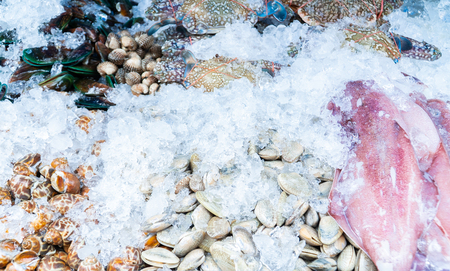 Top view. Fresh seafood piled soak with ice on street market. Фото со стока
