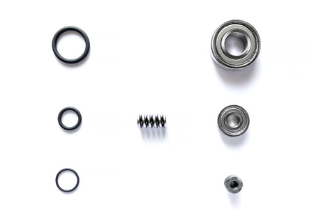 Top view of spare parts is bearing with tire ring and spring are small placed on white floor.