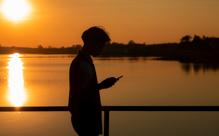 Silhouette of young man is using a smartphone. Standing on the banks of river. During sunset time.