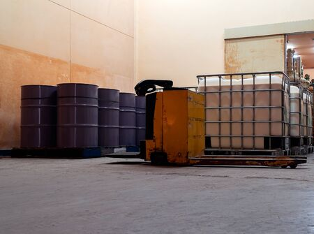 Low light inside of the factory. The large white and purple tanks chemical packaging. Stock Photo