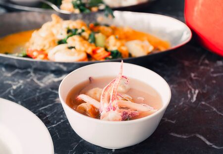 Close up view and dark color tone. Squid pieces in a cup which is part of cooking is Thai Seafood Spicy Soup.