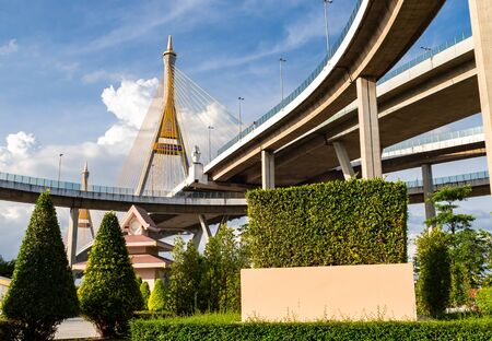 Bridge in Thailand. Look up view and shade. Cornerstone with large wire rope on the Industrial Ring Road. Under are public park. Translation on pole text