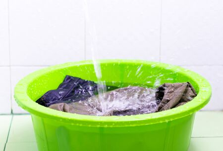 Overexposed and close up. Pour water into the green basin to soak the clothes before washing. There are splash water drops.