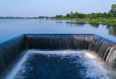 Outdoor and shade of small dam with water flowing rapids. Seen as lines and patterns with foam. The natural swamps abundant and surrounded by forests in the countryside of Thailand.