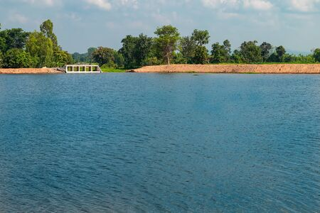 Wide view of watercourse concrete dam of water flowing on riverside for drainage in the countryside of Thailand.