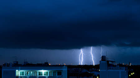 Severely lightning thundering down at urban in night. During the monsoon season.