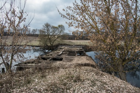 Old wooden abandoned bridge. Autumn on the river.