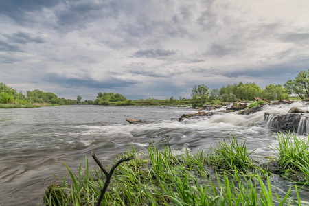 Summer landscape. River, riverside and sky. Rolls on a mountain river under the blue sky Archivio Fotografico