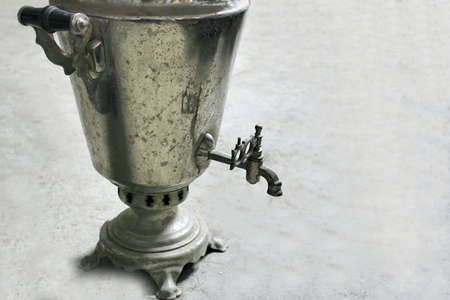 One old worn steel samovar on a gray concrete floor.