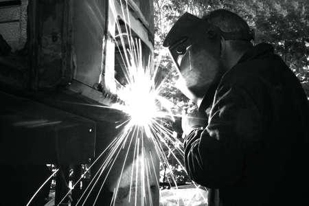 Welder welds metal on machine with sparks