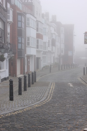 an old cobblestreet in sallyport portsmouth during a foggy day photo