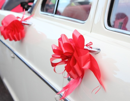 a vintage white wedding car with red ribbon photo