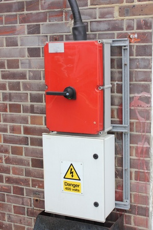 an industrial electrical supply box situated and fitted on the exterior wall of the building photo