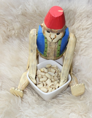 monkey nuts: A wooden monkey wearing a fez eating nuts