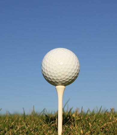 golf ball on a wooden tee with a blue sky background photo