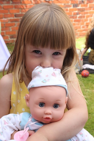 dearly: a contented looking young girl with her baby doll which she loves dearly