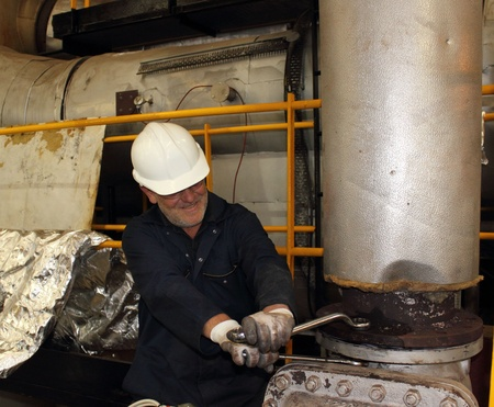 An engineer working on a steam valve on top of a 60,000lbs an hour boiler