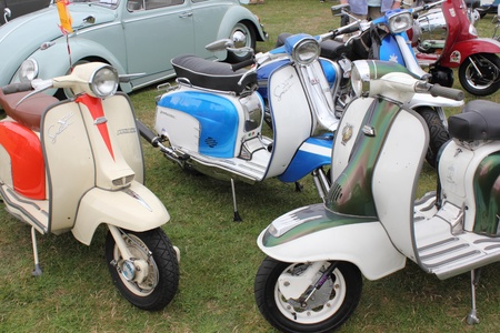 A collection of retro scooters with an old retro car in the background at a show in england ,12th august 2012