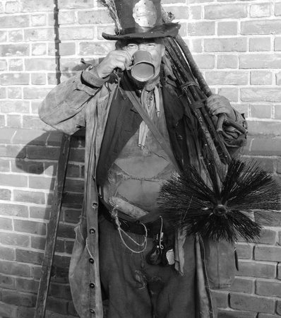 Victorian chimney sweep wearing his old clothes & carrying his brush