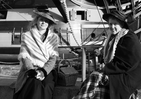 Victorian women sitting with an old wooden warship in the background,portsmouth,1st december 2012 Stock Photo - 17435816