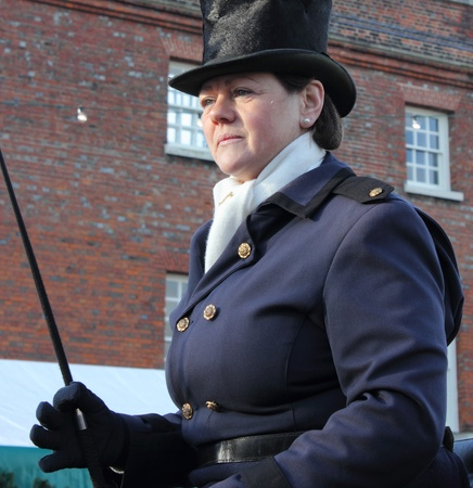 A woman riding a horse wearing her top hat and whip in hand,portsmouth dockyard,1st december 2012
