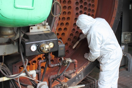 ingenieria industrial: Un ingeniero uso del PPE para limpiar una caldera industrial Foto de archivo