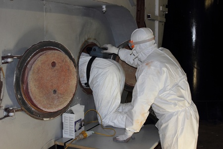 engineer s wearing ppe for an industrial boiler clean inside the furnance photo