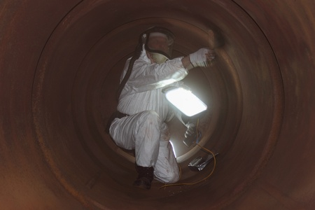 An engineer wearing ppe for an industrial boiler clean inside the furnance photo
