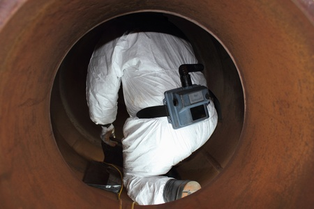 An engineer wearing ppe for an industrial boiler clean inside the furnance