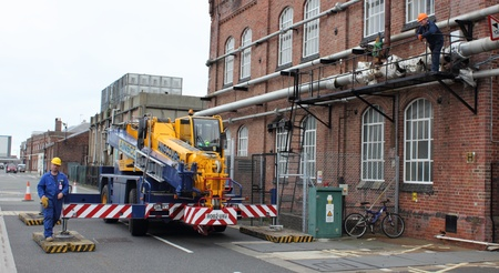 boiler house: A crane working outside a boiler house with slingers Editorial