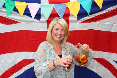 A british lady celebrating with a drink with the union jack and bunting in the background photo