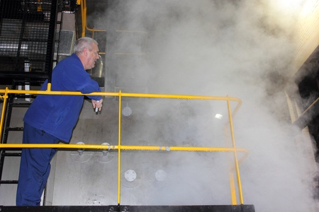 A boiler operator investigating a steam leak on an industrial steam boiler,12th oct 2012 Stock Photo - 17522995
